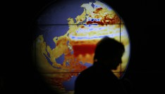 A woman walks past a map showing the elevation of the sea in the last 22 years during the World Climate Change Conference 2015 at Le Bourget